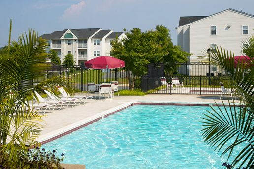 Fenced in pool with sun chairs, patio table with umbrella and seating